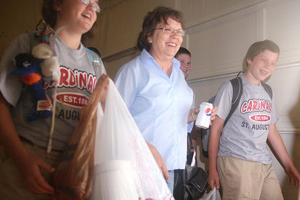 Teacher Sugar Hamilton, center, leads her homeroom students to class with the opening bell of the school year.