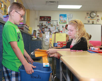 Mark Nulle, left, collects pencils from Erica Richardson in Patti Davis' third-grade class at Glasscock Elementary School.