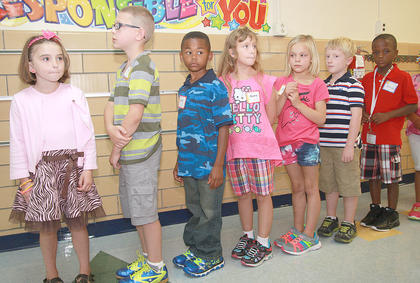 From left, Kaylee Powell, Terry Smith, David Smalley, Alanna Murphy, Bailey Coulter, Jaxson Hibbard, and Antwan Bickett line up in the hallway on the first day at Glasscock Elementary School. They are in Alicia Kelly's second grade class.