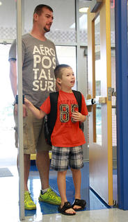 Second-grader Jason West takes a look around before entering Glasscock Elementary School with his dad, Michael.