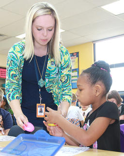 First-grade teacher Devin Reynolds helps Xiamiah Scott with Play-Doh at Glasscock Elementary School.
