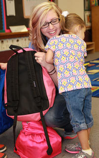 St. Augustine preschooler Whitney Elder clings to her mother, Kelly Elder, on the first day of school.