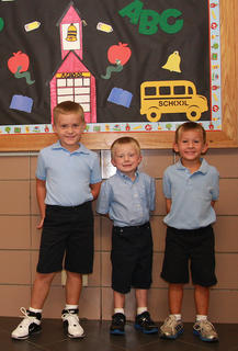 St. Augustine kindergartners Landon Bradshaw, Aiden Tatum and Nate Wright wait in the hallway.