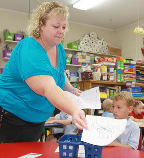 St. Augustine kindergarten teacher Cindy Bland passes out a coloring assignment on the first day of school. Eli George is seated at the table.