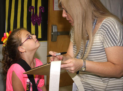 Hannah Fogle tells April Montgomery (WMES librarian) her bus number for afternoon pickup.