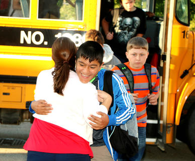 Noe Serrano gives teacher Deanna Bardin a big hug after getting off the bus at Marion County Middle School on the first day of school. Also pictured in the background is Nathan Long.