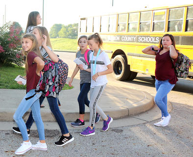 Students eagerly exit their school bus and walk toward the Marion County Middle School gymnasium on the first day of school.