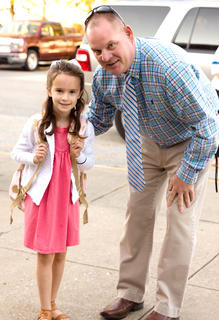 Alani Wheatley poses with West Marion Elementary School Principal Robby Peterson as she heads into school.