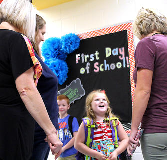 Staff greet Glasscock Elementary School student Brookelynn Riggs on opening day.