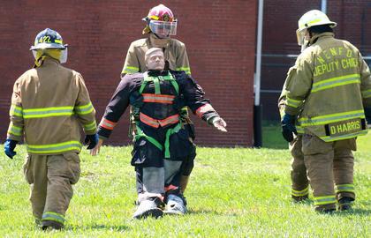 Donnie Curtsinger of the Northeast Nelson Fire Departments drags a 200-pound dummy in the last leg of the relay challenge as his teammates offer him encouragement.