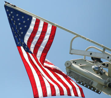 An American flag few from a ladder truck above the competition.