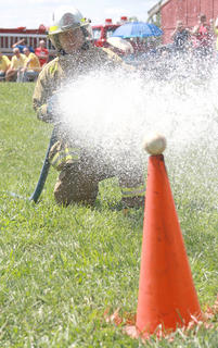 Derick Harris of the Northeast Nelson Fire Department was on target during the relay challenge, using the fire hose to knocking down softballs perched on orange cones.