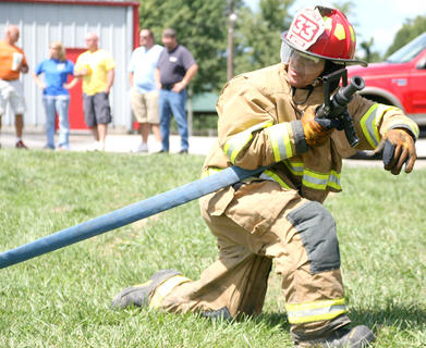 Keith Willett of the Loretto Fire Department prepares to move into a better position to hit a series of targets during a relay challenge.