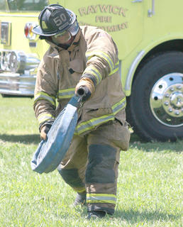 Mike Mullenhour of the Loretto Fire Department unrolls a fire hose at the start of a relay challenge.