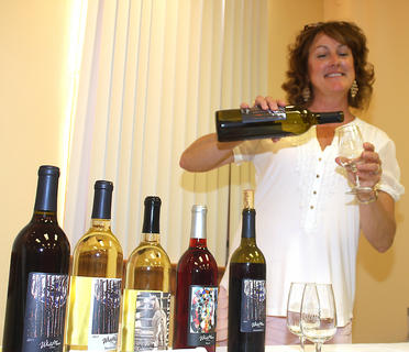 Alex Ackermann serves samples of wine from her WhiteMoon Winery before the play begins.