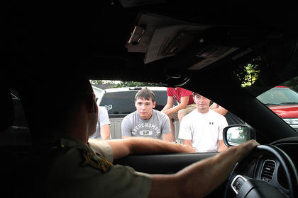 """Long summer days creep into the regular night time hours. It's past 8 p.m. and Marion County Sheriff's Deputy Courtney Deering slows down to talk with some Loretto youth. Here, he talks playfully with Nathan Shewmaker and Levi Hayden, among others. Deering has worked for the Marion County Sheriff's Department for the last four years, and worked for the Lebanon Police Department for a year prior. """"It's not all about arresting and giving tickets,"""" Deering said. It's also about helping others."""
