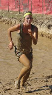Sara Higdon Thurmond finishes up the Muddy Mayhem obstacle and heads toward the finish line.