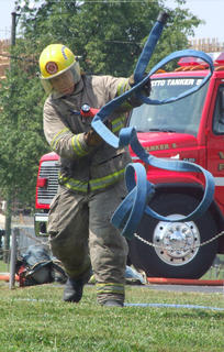 Loretto firefighter Mike Wiley tries to unroll a hose at the start of the obstacle course event.