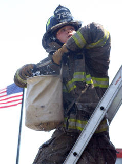 Matthew Riggs of the Raywick Fire Department passes a bucket of water up the ladder in the bucket brigade race.