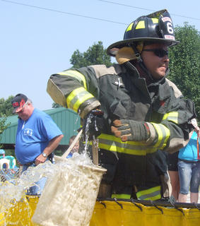 Jamie Lewis of the Gravel Switch Fire Department scoops up a bucket of water in the bucket brigade race.