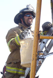 Frankie Skimmerhorn of the Loretto Fire Department passes a bucket of water up the ladder in the bucket brigade race.