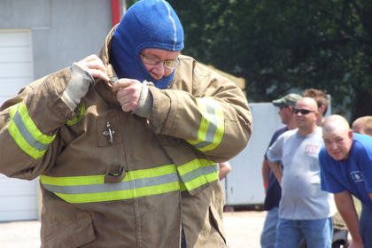Jim Thomas races to get into gear as his Loretto Fire Department teammates watch.