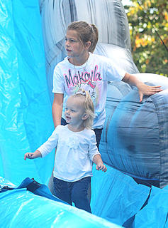 Makayla Mattingly, 9, and Alivia Alvey, 1, walk down the tunnel after a trip down a bouncy slide.