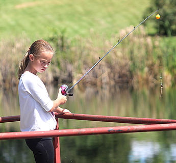 Katie Ruffing, 10, pulls her fishing line out of Badin Pond before casting it again.