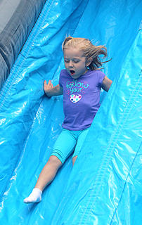 Olivia McCauley, 4, enjoys a trip down the bouncy slide.