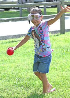 Jayla Penn, 6, sways as she tries to keep balance while wearing goggles that impair a person's vision.