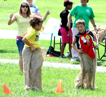Deanna Bradshaw (back) cheers on Aaron Leake, 10, (left) and Landon Sims, 8, (right) of Georgetown, as they hop towards the finish line.