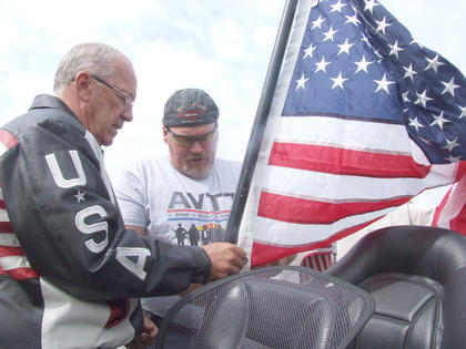 Mike Kays (USA jacket) of Springfield and Jimmy Wright of Lebanon attach an American flag to Kays' motorcycle before Saturday's ride.