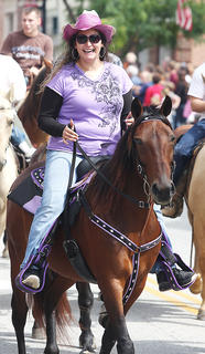 Taneasha Boswell is stylin&#039; in purple as she rides in the Pigasus Parade. Her horse even had a purple saddle.