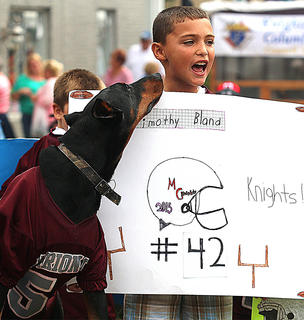 Timothy Bland and a German Pinscher named Hulk show off their Knight pride riding a float with Marion County Youth Football during the Pigasus Parade.