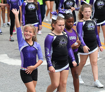 Brooklyn Mattingly waves to the crowd as she and her fellow Fit Kids gymnasts walk in the Pigasus Parade. Also pictured is Mia Mattingly, Honesty Porter and Riley Cox.
