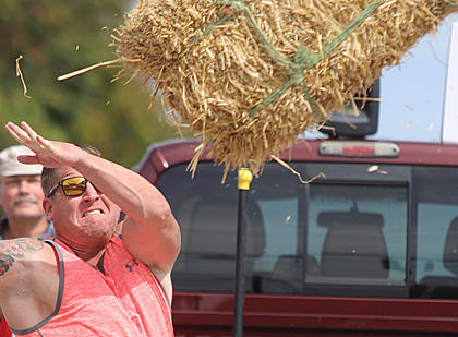 Steven Farmer releases the hay bale during his final throw in the men's division on Sunday afternoon.