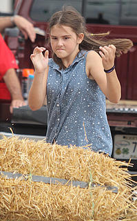 Cheyenne Conley gives her best effort in the hay bale toss.