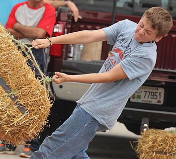 Blake Warner puts his full effort into his throw in the boys division of the hay bale toss.