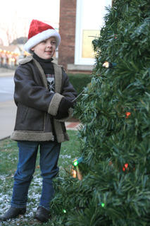 Trey Murphy, 5, uses his magic wand to turn on the lights of the Christmas tree outside the Marion County Courthouse at the start of Dickens Christmas festivities.