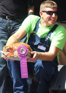Marion County High School FFA advisor and agriculture teacher Daniel Mattingly holds the champion country ham that was auctioned off Saturday morning. The ham was cured by Tyler Jones, a student in the FFA/4H programs at Marion County High School.