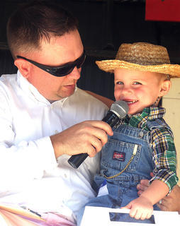 Junior Farmer participant Ashton Boyd smiles at the crowd as Jeremy Bowman asks him questions on stage.