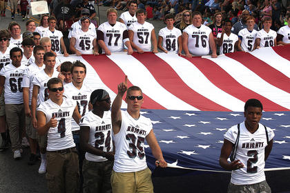 The Marion County High School football team carries the American flag at the start of the PIGasus Parade.