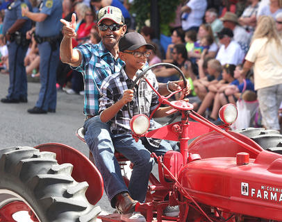 John King allows his grandson to take the wheel during the PIGasus Parade.