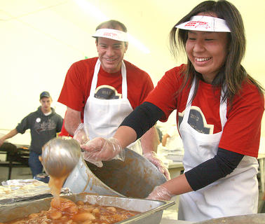 Maki Kamimura transfers baked apples to a serving tray with some help from Dennis Brown Saturday morning at the Dunn Chrysler Country Ham Breakfast.