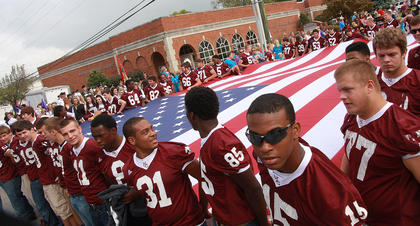 The Marion County High School football team lines up near the Marion County Public Library to carry a big American flag in the Spring View Hospital Pigasus Parade.