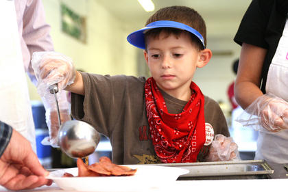 Joe Keith Shewmaker, 7, serves up red-eye gravy Sunday morning at the Dunn Chrysler Country Ham Breakfast.