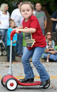 Lydia Bennett rides her scooter in the parade with the Spring View Hospital group.