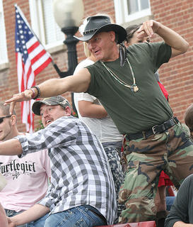 The Turtleman Ernie Brown Jr. works the crowd as he travels down Main Street during the Pigasus Parade.