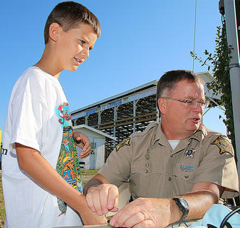 Marion County Sheriff Jimmy Clements scans Connor Zink's finger for his Kid Print ID card.