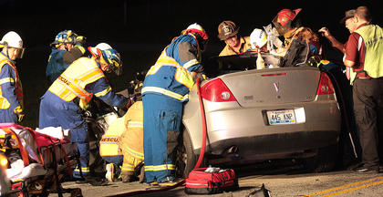 Marion County emergency personnel work to free Jared Wheatley after a two-vehicle collision Sunday evening on the Marion County Veterans Memorial Highway. A Loretto man, James Clayton Tharp, died in the accident. This was one of multiple fatal accidents in 2011.